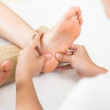 A therapist providing reflexology services to a pregnant woman